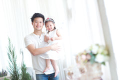 Family, child and home concept - smiling parents and little girl Stock Photo