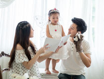 Family, child and home concept - smiling parents and little girl Stock Photography