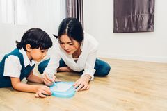 Family child kid boy son kindergarten and beautiful mother education teaching drawing together. At interior room home stock image