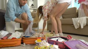 Family with child packing luggage for journey. Young family with child packing a luggage for a new journey stock video footage