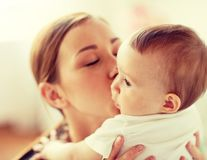 Happy young mother kissing little baby at home stock photos