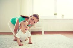 Happy mother playing with baby at home stock photography