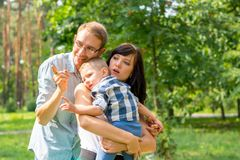 Family with a child in the park looks at something interesting. Dad hugs mom who holds the child in her arms. Family resting in the park in sunny day Royalty Free Stock Photos