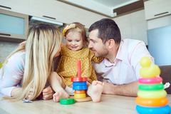 A family with child plays board games sitting at a table. stock photography