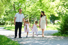 Family with child and pregnant woman walk in summer city park Stock Photos