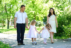 Family with child and pregnant woman walk in summer city park Royalty Free Stock Images