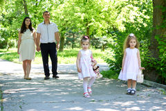 Family with child and pregnant woman walk in summer city park Stock Images