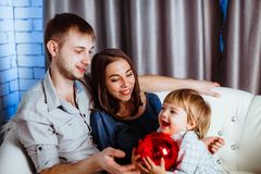 A family with a child sitting on the couch Stock Photo