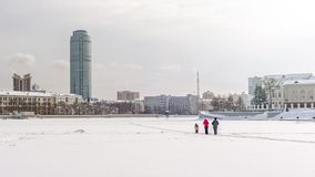 Family with child skiing on a cloudy winter day on the frozen city pond stock photos