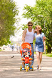 Family with child in stroller walking across park stock photos