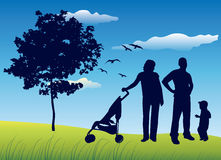 Family with child on summer field. Family with little child on summer field near tree with carriage, blue sky Stock Images