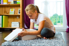 Family - child or teenager open a gift. Or box at home in the living room Stock Image