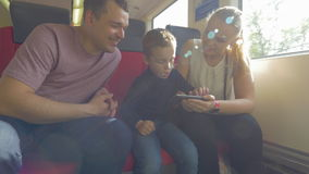 Family with child traveling by train and using cell. Parents and little son traveling by train. Mother and father trying to entertain sad and bored child with stock video