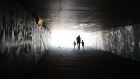 Family child underground. Man with children girls walk through underground dark passage subway toward light stock video