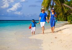 Family with child walking on sand beach Stock Photos