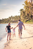 Family with child walking together on the beach shore during vacation Royalty Free Stock Photography