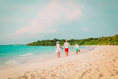 Family with child walking on beach. Family with child walking on tropical beach, vacation concept royalty free stock photo