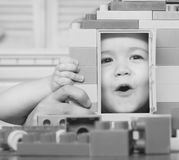 Family and childhood concept. Kid looking through door of toy house made of plastic blocks. Child plays with. Construction bricks. Boy holds toy house on light royalty free stock image
