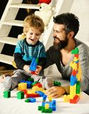 Family and childhood concept. Man and boy play together. Father and son with happy faces create colorful constructions with toy bricks. Dad and kid with ladder stock photo