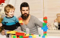 Family and childhood concept. Man and boy play together. On wooden wall background. Dad and kid build of plastic blocks. Father and son with happy faces create stock image