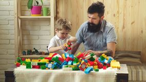 Family and childhood concept. Man and boy play together on wooden wall background. Dad and kid build of plastic blocks. Father and son with busy faces create stock video footage