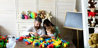 Family and childhood concept. Young family spends time in playroom. Mom, dad and boy with toys on behind build out of plastic blocks. Parents and son with stock photo