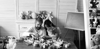 Family and childhood concept. Young family spends time in playroom. Mom, dad and boy with toys on behind build out of plastic blocks. Parents and son with royalty free stock photo