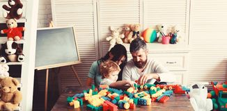 Family and childhood concept. Young family spends time in playroom. Mom, dad and boy with toys on behind build out of plastic blocks. Parents and son with royalty free stock image