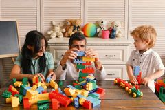 Family and childhood concept. Young family spends time in playroom. Mom, dad and boy. With toys on room background build out of plastic blocks. Parents and son stock photos
