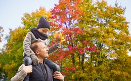 Happy father carrying son with autumn maple leaves stock photography