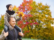 Happy father carrying son with autumn maple leaves stock images