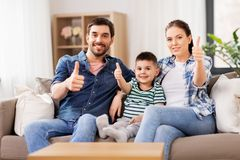 Portrait of happy family showing thumbs up at home. Family, childhood and fatherhood concept - portrait of happy father, mother and little son sitting on sofa stock image