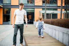 Family, childhood, fatherhood, leisure and people concept - happy young father and little daughter stroll through the streets of t royalty free stock photo