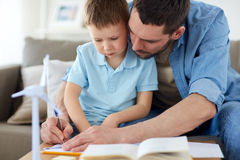 Father and son with toy wind turbine at home Stock Image