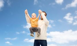 Father with son playing and having fun. Family, childhood, fatherhood and people concept - happy father and little son playing and having fun over blue sky and Stock Images