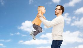 Father with son playing and having fun. Family, childhood, fatherhood and people concept - happy father and little son playing and having fun over blue sky and Royalty Free Stock Images