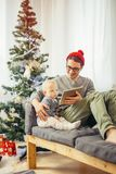 Baby with father sitting and using digital tablet during Christmas Royalty Free Stock Photography