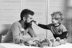 Family and childhood. Man with beard and boy play together. Family and childhood concept. Man with beard and boy play together on wooden wall background. Dad and royalty free stock image