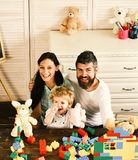 Family and childhood. Mom, dad and boy play with toys. Family and childhood concept. Mom, dad and boy play with white soft toys on room background. Parents and royalty free stock images