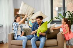 Happy family having pillow fight at home. Family, childhood and people concept - happy father, mother, little son and daughter fighting by pillows and having fun royalty free stock image