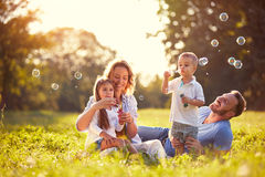 Family with children blow soap bubbles. Nature
