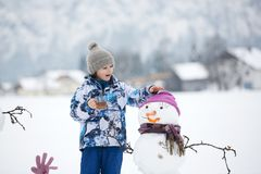 Family with children, building snowman in the park in little village in Austria royalty free stock photography