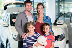 Family with children buying new car at auto dealership Royalty Free Stock Photography