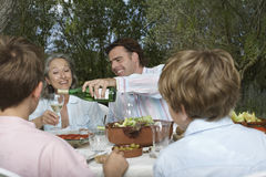 Family With Children Dining In Garden Stock Photo