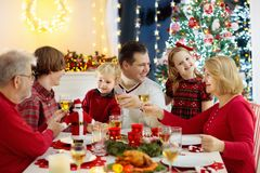 Family with children eating Christmas dinner at fireplace and decorated Xmas tree. Parents, grandparents and kids at festive meal stock images
