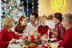 Family with kids having Christmas dinner at tree stock photography