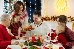 Family with kids having Christmas dinner at tree royalty free stock photos