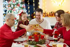 Family with children eating Christmas dinner at fireplace and decorated Xmas tree. Parents, grandparents and kids at festive meal royalty free stock photos