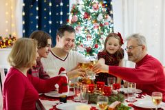 Family with kids having Christmas dinner at tree royalty free stock photography