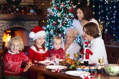 Christmas dinner. Family with kids at Xmas tree. Family with children eating Christmas dinner at fireplace and decorated Xmas tree. Parents and kids enjoy Stock Photos
